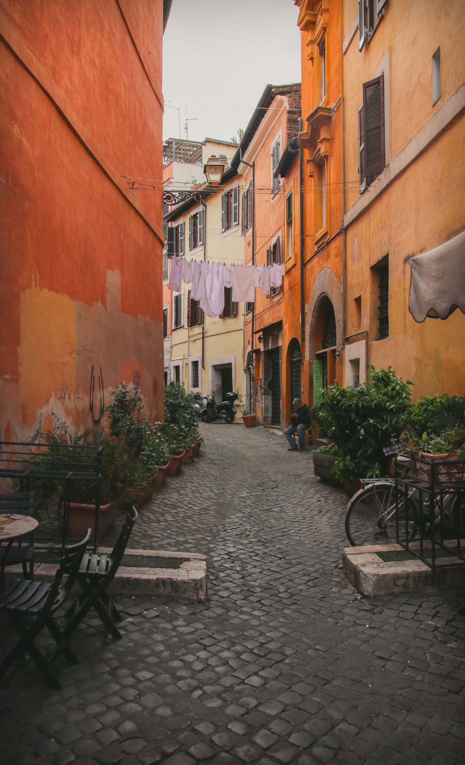 Cobblestone street with orange buildings and hanging laundry in Trastevere, Italy.