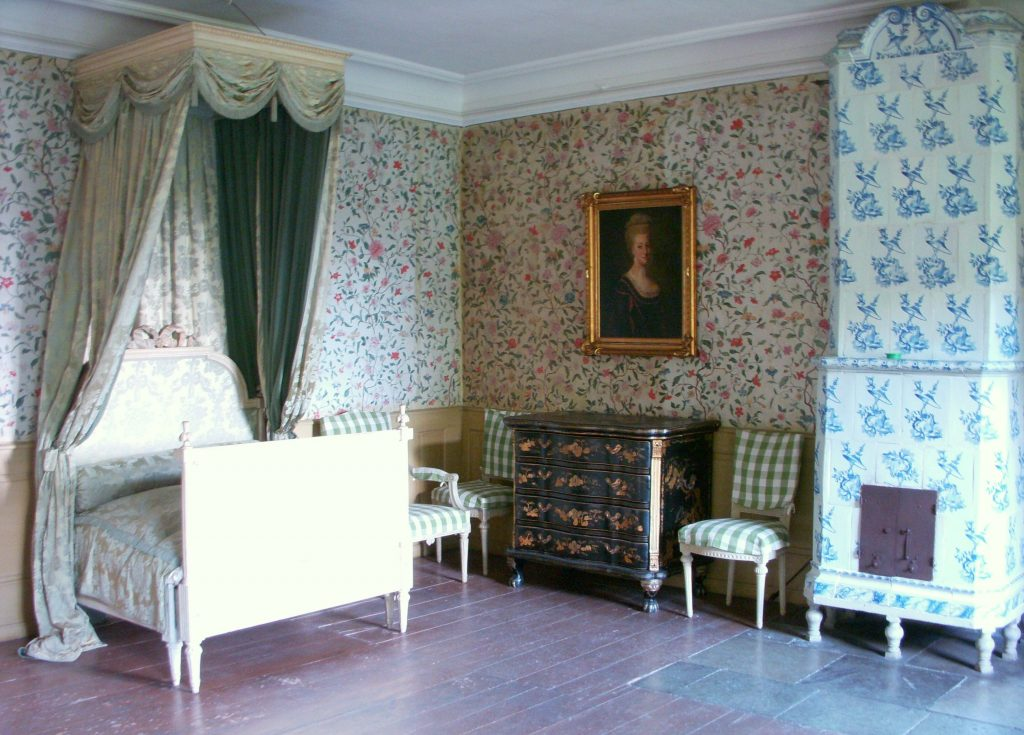 green gingham upholstered chairs, blue tiled stove, pink flower wallpaper